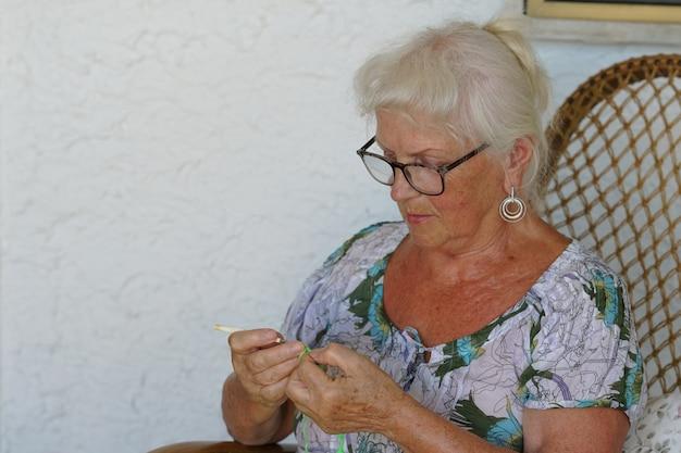 Пожилая женщина занимается вязанием в свободное время