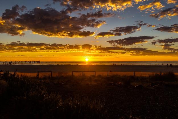オーストラリア、アデレードのグレネルグビーチで輝く夕日の海景。