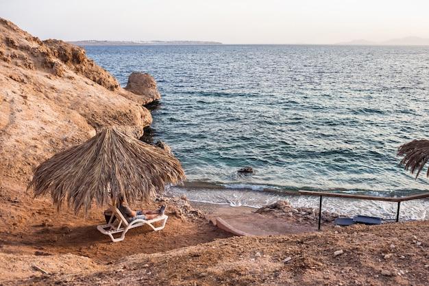 男は海と砂浜を背景にラウンジャーにあります。