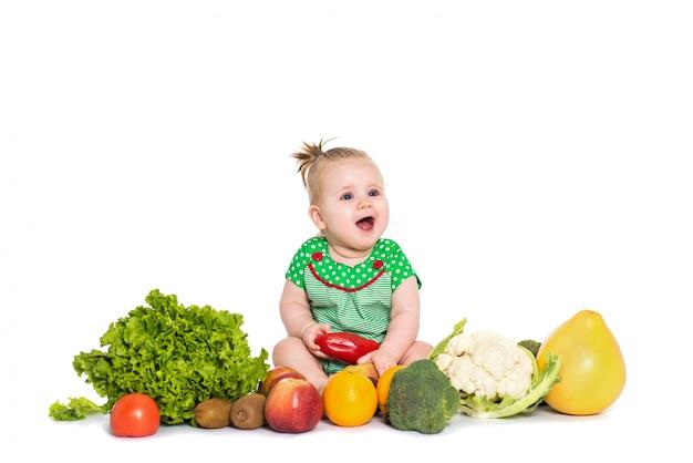 女の赤ちゃん、白で隔離され、果物や野菜に囲まれて座っています。