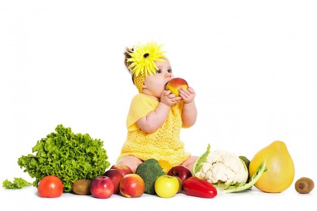 女の赤ちゃんは白で分離された野菜や果物の周りです。