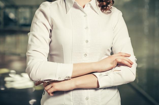オフィスのクローズアップで手でジェスチャーを行うビジネス女性