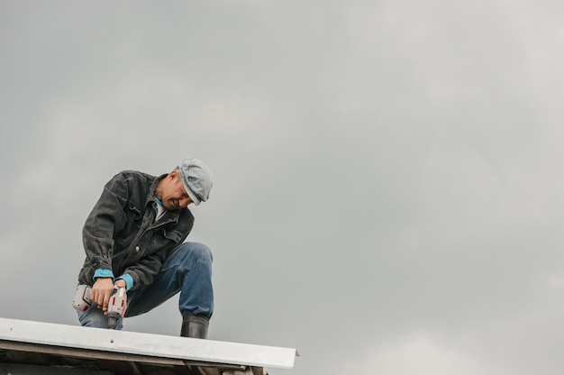 Мужчина в рабочей одежде затягивает винты отверткой на крыше на фоне облачного неба