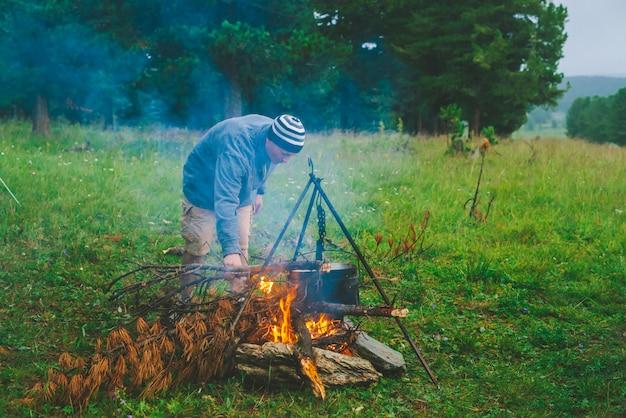 旅行者はキャンプで火をつけています。
