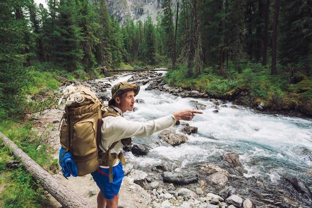 山の川に沿って途中の旅行者。