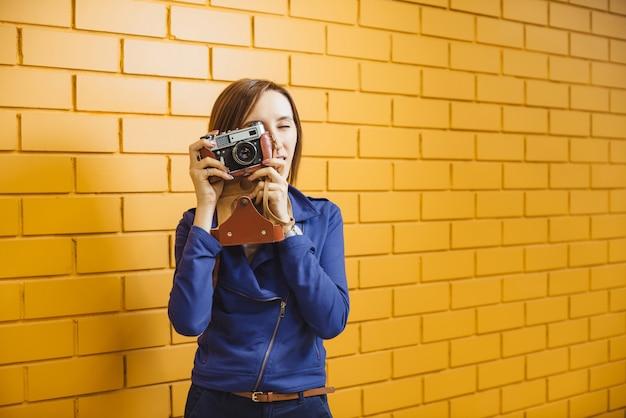 黄色のレンガの壁にレトロな金属フィルムカメラで美しい狂気の少女。