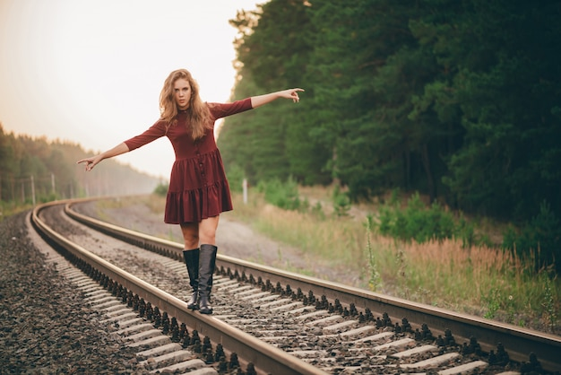 巻き毛の自然な髪の美しい夢のような女の子は、鉄道の森で自然を楽しみます。
