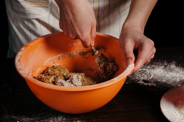 暗いキッチンのエプロンの女の子がオレンジ色のカップで生地をこねます。