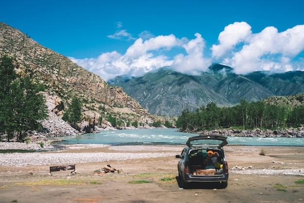 Автомобиль с открытым большим багажником возле горной реки с бирюзовой водой.