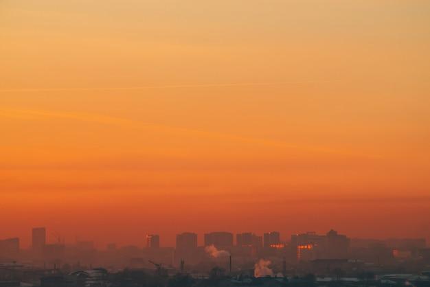 日没の民家の背後にある都市の高層ビル。