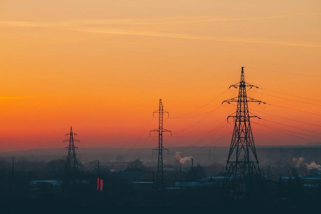 夜明けの都市の送電線。
