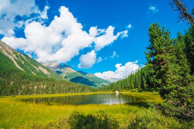 白い雲と青い空の下で巨大な山の前に美しい山の湖。