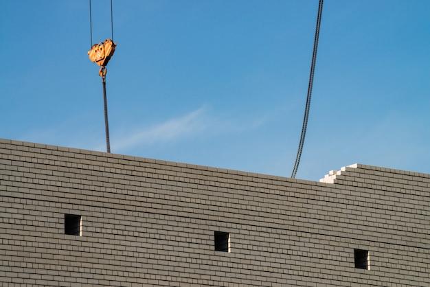 Крюк башенного крана над незаконченным зданием в строительной площадке. фоновое изображение белой кирпичной стены под голубым небом. фоновое изображение процесса строительства.