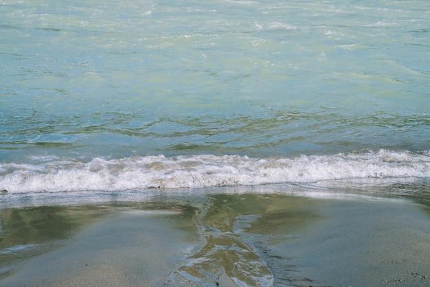 Детальная текстура поверхности воды и песка бирюзы спеша. пороги горной реки крупным планом. предпосылка волн чистой воды на пляже.
