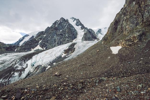 山脈の雪。曇り空の下で雪に覆われた大気の尾根。どんよりした天気の中で異常な巨大な岩。山に登る。高地の雄大な自然の驚くべきミニマルな風景。