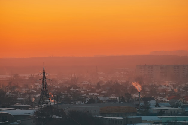 Линии электропередач в городе на рассвете. силуэты городских зданий среди смога на восходе солнца. кабели высокого напряжения на теплом небе оранжевого желтого цвета. энергетика на закате. городское электроснабжение. городской фон тумана.