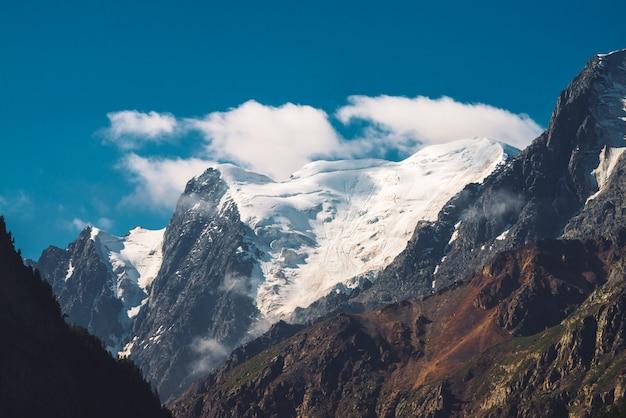 Низкие облака и туман на вершине горного хребта. ледник под ясным голубым небом. снежный горный пик в солнечный день. гигантский скалистый хребет со снегом. атмосферный минималистичный горный ландшафт величественной природы.