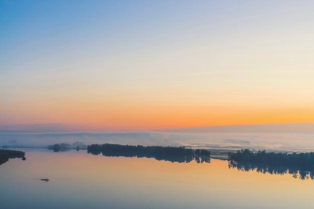 広大な神秘的な川が対岸に沿って流れ、木のシルエットと濃い霧が流れています。夜明け前の空に金の輝き。温かみのある色調の雄大な自然の穏やかな朝の大気の風景。