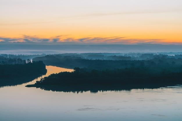 深い霧の中の森林に沿って、広い川が海岸に沿って流れています。早い青空が水に反映されます。絵のように美しい夜明けの空に黄色のストライプ。雄大な自然の神秘的な朝の大気の風景。