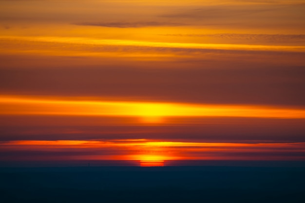 Большой красный круг солнца поднимается из-за темного горизонта на разноцветных облаках теплых оттенков. красивая предпосылка рассвета на живописном небе облака. солнце в центре.