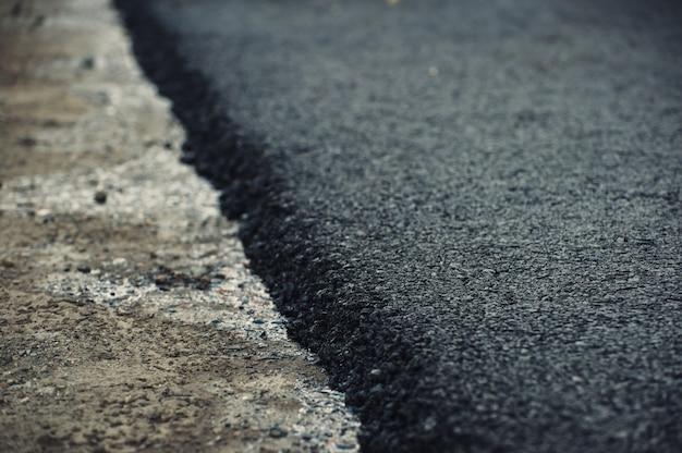 Часть свежего асфальта крупным планом. строительство и ремонт дорог.