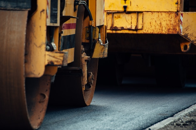 Желтый асфальтовый уплотнитель выравнивает дорогу. укладка нового асфальта.