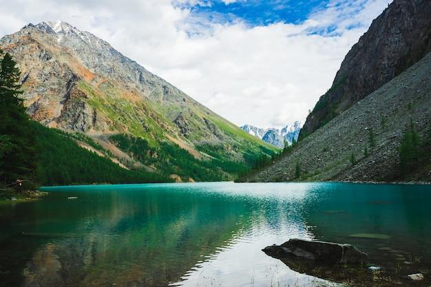 Горное озеро возле огромной скалистой горы со снегом. прекрасный ледник. удивительный гигантский снежный хребет. валуны в чистой блестящей воде. прекрасный атмосферный ландшафт величественной природы высокогорья.
