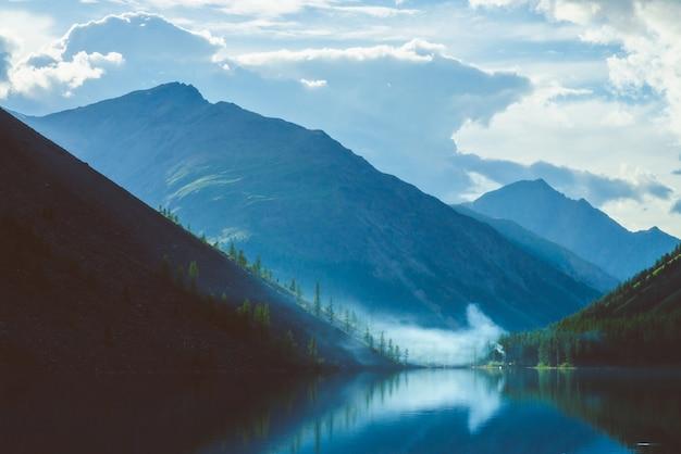 早朝の高地の幽霊のような山の湖。山と雲の美しい霧のシルエットは、澄んだ水面に反映されます。キャンプファイヤーの煙。雄大な自然の素晴らしい風景。
