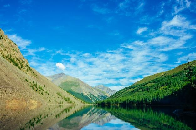 Прекрасное горное озеро в долине горной местности. гигантские горы отражаются в гладкой чистой поверхности воды. удивительный хвойный лес в солнечном свете. атмосферный яркий зеленый пейзаж величественной природы.