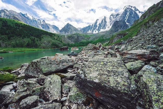 山の湖は、巨大な美しい氷河の前にある大きな石と岩に囲まれています。ピラミッドの形をした素晴らしい山。曇り空の下で雪の尾根。素晴らしい大気の風景。