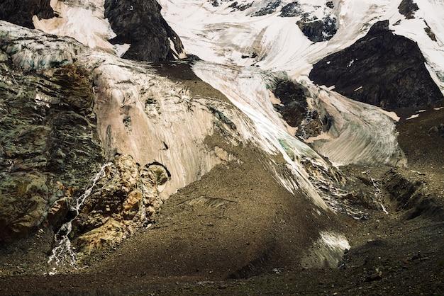 巨大な氷河のふもと。雪と氷の素晴らしい岩の救済。小さな滝のある素晴らしい巨大な山の岩壁。氷河からの水。雄大な高地の自然の素晴らしいアートワーク。
