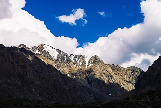 Снег на гигантском скалистом гребне под голубым облачным небом. темный крутой склон горы. удивительная снежная горная цепь в солнечном свете. прекрасные скалы. атмосферный солнечный пейзаж величественной природы высокогорья.