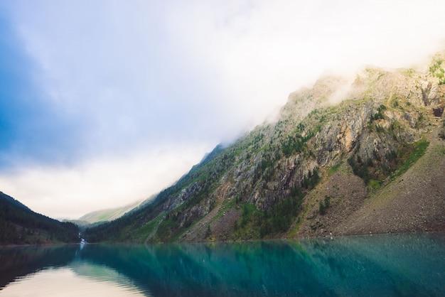 Гигантские скалы с деревьями в утреннем тумане отражается в воде горного озера. раннее солнце светит сквозь туман. пасмурная погода. атмосферный горный ландшафт величественной природы.