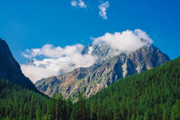晴れた日の巨大な岩。針葉樹林に覆われた丘の後ろに雪で岩が多い尾根。青空の下で巨大な雪山の上の雲。雄大な自然の大気の高地の風景。
