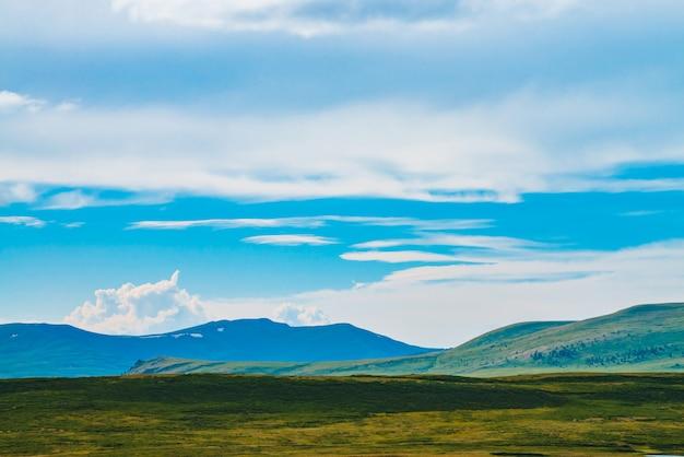 雪と壮大な景色の巨大な山々。山の上の巨大な雲。奈落の底の大きな岩の崖。素晴らしい野生の風景。雄大な自然の大気の高地の風景。風光明媚な山の風景。