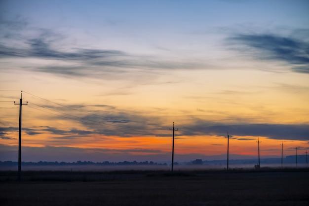 日の出背景にフィールドの電力線。夜明けにワイヤーが付いている棒のシルエット。暖かいオレンジ色の青い空に高電圧のケーブル。日没時の電力産業。色とりどりの絵のような鮮やかな空。