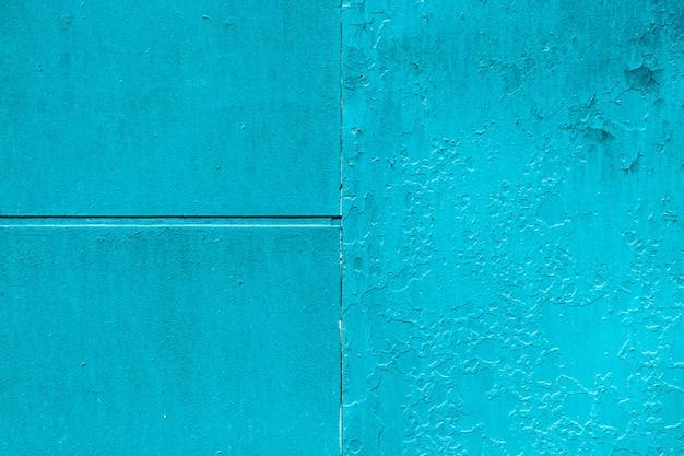 不完全な金属板。ひびの入った塗料のクローズアップ。マクロのテクスチャを損傷します。汚れた金属パネル。織り目加工の背景。大まかな色あせた不均一な鉄の壁。廃止された表面。古い塗料の剥離。染料の剥離