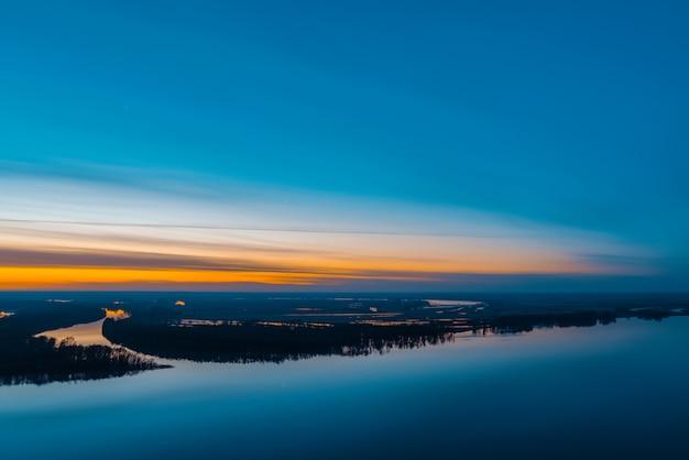 夜明け前の空の下の木と大きな島の美しい川。美しい曇り空の明るいオレンジ色のストライプ。早い青空が水に反映されます。雄大な自然のカラフルな朝の大気イメージ。