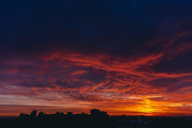 燃えるような赤い血の吸血鬼の夜明け。驚くほど暖かく劇的な火の青い暗い曇り空。オレンジ色の日光。どんよりした天気の日の出の大気の背景。激しい曇り。嵐雲の警告。コピースペース