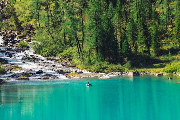 Горный ручей впадает в озеро. взгляд над рыболовом в шлюпке на лазурной воде. прекрасный лес в солнечном свете. большие валуны в ручье. атмосферный красивый пейзаж горной природы в солнечный день.