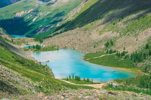 Прекрасные три горных озера в долине горной местности. очистить лазурную поверхность воды. гигантские скалы и горы с богатой растительностью и хвойным лесом. атмосферный зеленый пейзаж величественной природы