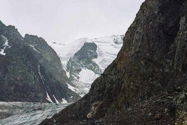 山脈の雪。曇り空の下で大気の雪の尾根。曇りの天気の中で素晴らしい巨大な岩。山に登る。高地の雄大な自然の驚くべきミニマルな風景。