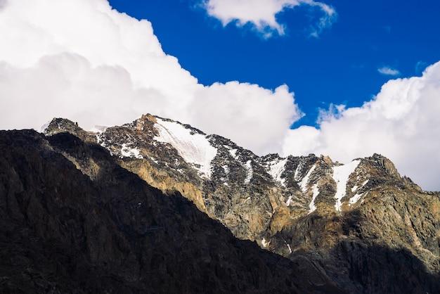 青い曇り空の下で巨大な岩の尾根に雪が降る。暗い急な山腹。日光の下で驚くほど雪に覆われた山脈。素晴らしい岩。高地の雄大な自然の大気の晴れた風景。
