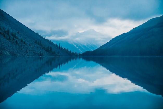 山と低い雲の素晴らしいシルエットが山の湖に反映されます。水ミラーの美しい波紋。高地の曇り空。大気の幽霊のような風景。素晴らしい神秘的な山の風景。
