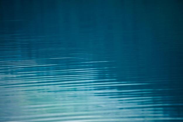 穏やかな青いきれいな水面の素晴らしいテクスチャ背景。山湖のクローズアップのサンシャイン。晴れた日の光沢のある水に美しい波紋。素晴らしいリラックステクスチャ。