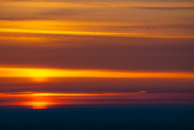 Большой красный солнечный круг поднимается из-за темного горизонта на фоне разноцветных облаков теплых оттенков.
