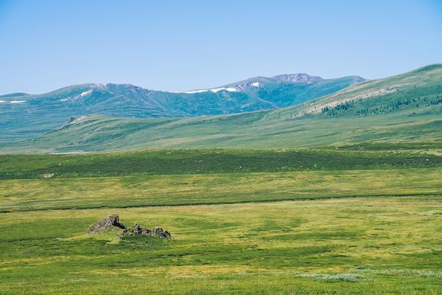 澄んだ青い空の下で雪と巨大な山に対する緑の谷の岩。