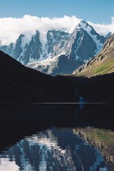 Изумительный ледник под голубым небом. ридж со снегом отражается на горном озере.