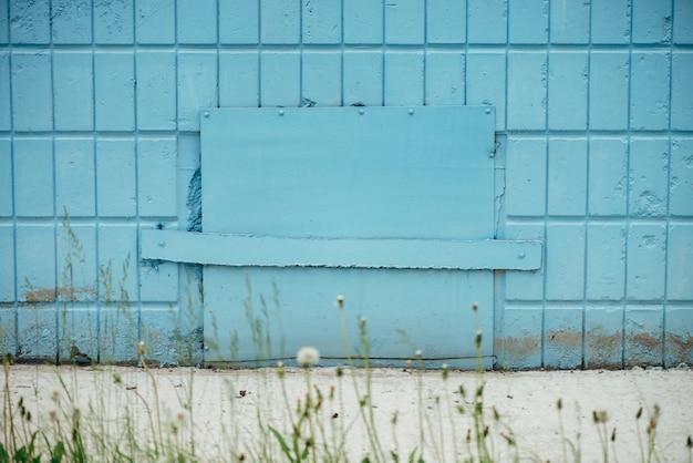 Синий люк в стене здания