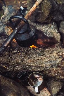 Кипение чая в чайнике на костре с большими дровами